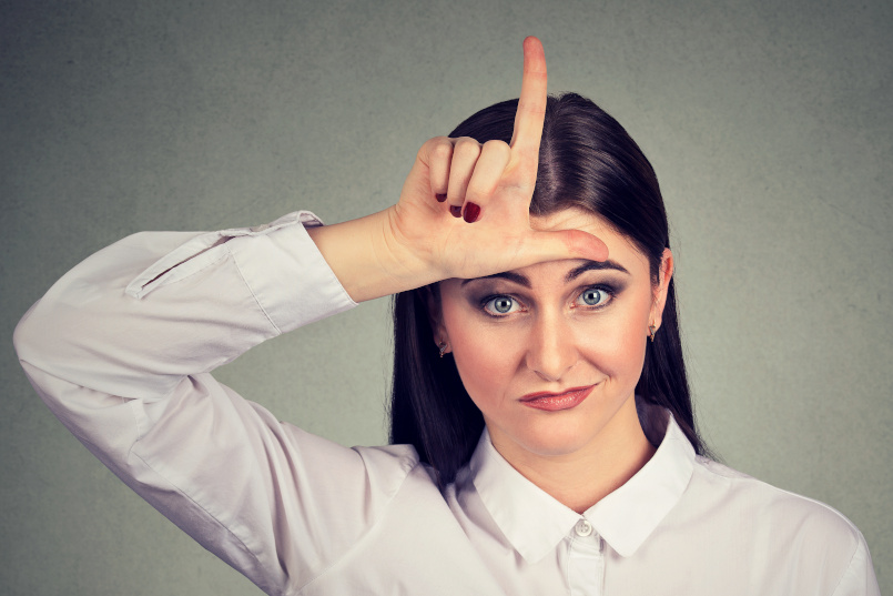 Angry woman showing loser sign looking at camera